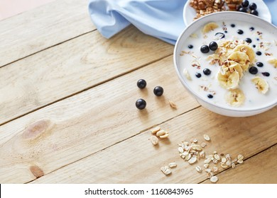 Oatmeal porridgewith bananas, nuts, raisins, blueberries and milk on table on wooden  background.  Healthy breakfast and diet food. Top view