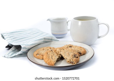 oatmeal raisin cookies, one broken in half, on a plate with a cup of coffee