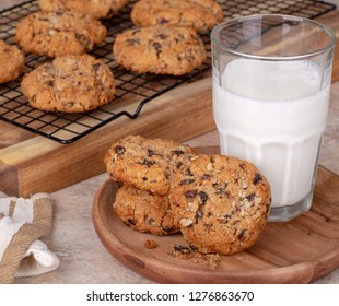 Oatmeal raisin nut cookie and glass of milk on a wooden plate with cookies on a cooling rack in background