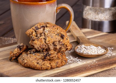 Oatmeal raisin nut cookies and oatmeal flakes on a wooden surface with a coffee cup