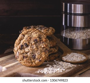 Oatmeal raisin nut cookies and oatmeal flakes on a wooden board against a dark wood background
