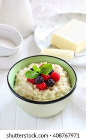 Oatmeal with raspberries and blackberries and mint in a bowl on a white background