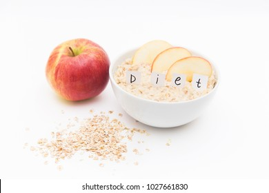 Oatmeal in a white plate and red apple on a wooden background