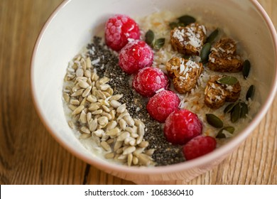 Oatmel with raspberries, sunflower, chia seeds, musli hearts and coconut