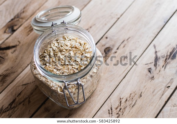Oats in bowl. Rustic wooden background.