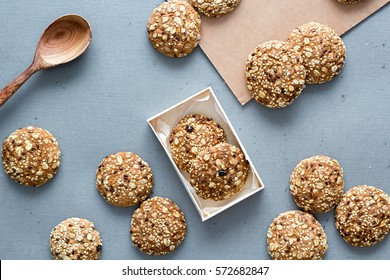 Oats cookies on a gray table in rustic style. seeds, baking in a box with a wooden spoon. Top view
