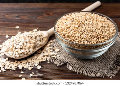 Oats and flakes on dark wooden background.