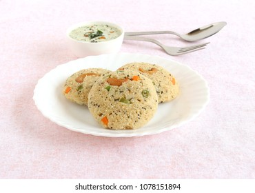 Oats Idli or cake, a healthy Indian vegetarian steam-cooked food, which also has vegetables like carrot, peas, green beans and capsicum, and cashew nuts, and coconut chutney.
