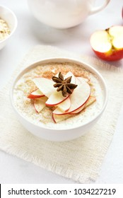 Oats porridge with red apple slices and cinnamon on white stone background. Healthy diet breakfast concept.