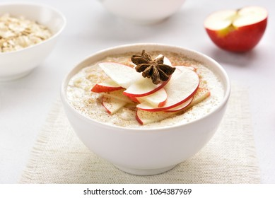 Oats porridge with red apple slices and cinnamon. Healthy diet breakfast concept. Close up view