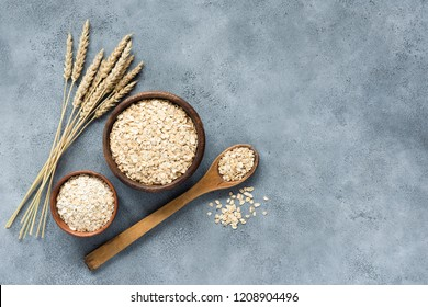 Oats, rolled oats and oat flakes in wooden bowl, top view. Concept of healthy eating, healthy lifestyle, dieting and vegetarian food