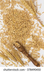 Oats are scattered on the table, a wooden spoon, wheat and barley