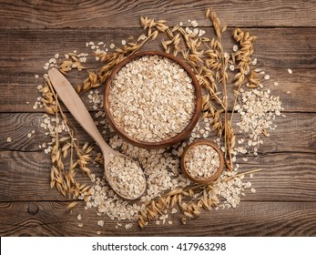 oats in a spoon in a plate on a table scattered oat flakes.
