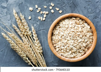 Oats in wooden bowl. Uncooked rolled oats. Oat flakes. Top view. Concept of healthy eating, dieting, healthy lifestyle, weight loss