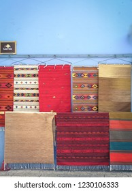 Oaxaca City, Mexico - August 9, 2015: Colorful rugs hang on a blue wall and being sold at the center of Oaxaca City.