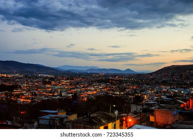 Oaxaca, Mexico. Aerial view of Oaxaca, Mexico at sunset. Mountains at the background, dark city with illuminated buildings at night