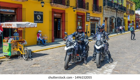OAXACA, MEXICO - AUGUST 24, 2019: Mexican Motorcyle Police Riding Down a Colorful Street in Oaxaca Mexico
