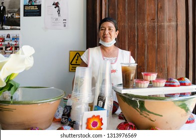 OAXACA, OAXACA, MEXICO- DECEMBER 2, 2018: Smiling woman posing with micoatole, chilacayota water and big clay casseroles with tejate, typical desserts and beverages in Oaxaca, Mexico