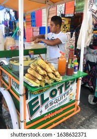 Oaxaca, Mexico - December 21 2018 - A man serving food from his elotes cart, in downtown Oaxaca.  Elotes are pieces of grilled Mexican street corn, often served with lime, cheese and spice.