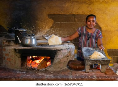 OAXACA, MEXICO - FEBRUARY 27, 2020: Smiling indigenous mexican woman with corn tortilla pancake making the traditional Tlayuda dish in colorful clothing by a fire.