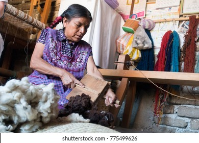 OAXACA, MEXICO - JANUARY 8, 2015: MAYAN WOMAN WORKING WITH WOOL USING TRADITIONAL TOOLS.