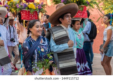 OAXACA, OAXACA, MEXICO- JULY 6, 2019: Young woman and man dressed with traditional clothes during the Convite, a party made for invite to a big traditional party called Guelaguetza in Oaxaca, Mexico