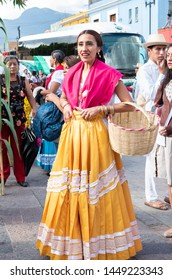 OAXACA, OAXACA, MEXICO- JULY 6, 2019: Woman dressed with traditional clothes during the Convite, a party made for invite to a big traditional party called Guelaguetza in Oaxaca, Mexico