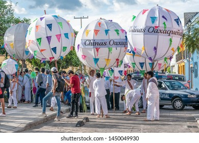 OAXACA, OAXACA, MEXICO- JULY 6, 2019: Young men dressed with traditional clothes and carrying big balls called marmotas during the festivities of Guelaguetza in Oaxaca, Mexico