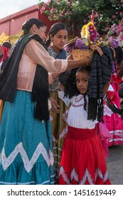 OAXACA, OAXACA, MEXICO- JULY 6, 2019: Women putting a basket on a girl's head during the Convite, a party made for invite to a big traditional party called Guelaguetza in Oaxaca, Mexico