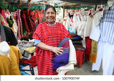 OAXACA, MEXICO - MARCH 7th, 2012: Smiling native mexican woman from Oaxaca region selling traditional mexican shawl and  clothes with embroidery on a street market in Oaxaca, Mexico