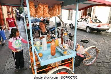 OAXACA, MEXICO - MARCH 7th, 2012: Woman selling fresh snacks, fruits and juices on a  central  street in  Oaxaca, Mexico