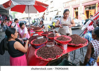 OAXACA, MEXICO - MARCH 8th, 2012: Women selling dried spiced grasshoppers (chapulines) on a local street market in Oaxaca, Mexico