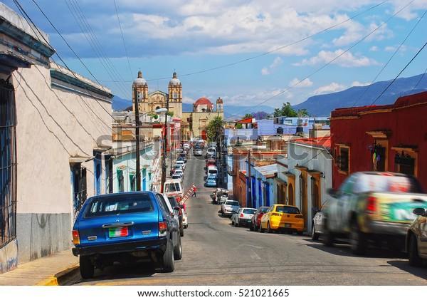 Oaxaca, México. Calles de la ciudad colonial de Oaxaca con coches aparcados, Iglesia y antiguo monasterio de Santo Domingo de Guzmán al fondo. Destino popular en México