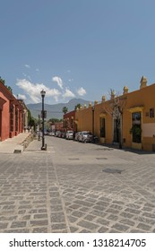 Oaxaca, Mexico-July 20, 2018: narrow cobblestone road with colorful buildings