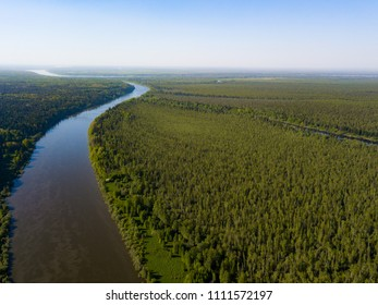Ob river flows through the taiga. River landscape, beautiful sky reflection in water. Vasyugan Swamp from aerial view. Tomsk region, Siberia, Russia