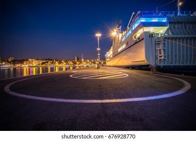 Obala kneza domagoja street at night with large ship docked - Harbour in Split, Croatia