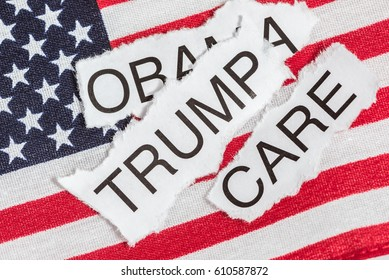 Obama Care in torn paper on the American Flag covered by the word Trump