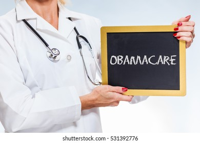 Obamacare Chalkboard Sign Held By Female Doctor.