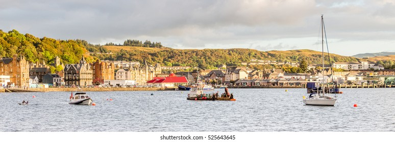 OBAN, ARGYLL, SCOTLAND - SEPTEMBER 24, 2014: waterfront and bay in a bright, sunny summer sunset. This harbour is the gateway to Mull and the islands, as well as fishermen base for seafood captures.