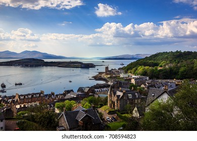 Oban Harbor. A scenic view from the hill above the sunlit port of Oban on the west coast of Scotland on a sunny summers afternoon. The ferries traverse the harbor to the outlying islands.