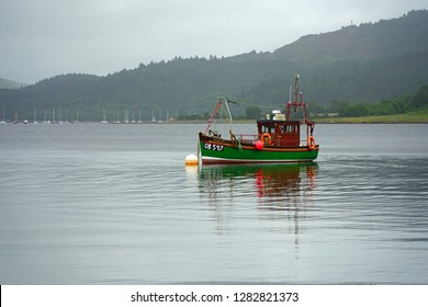 OBAN, SCOTLAND -15 JUL 2017- View of a small fishing boat in a Scottish bay near Oban, in Argyll and Bute, Scotland, under a grey, cloudy sky.