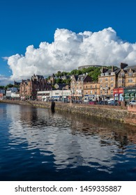 Oban, Scotland - June 7th 2019: A cloud is reflected in the sea over Oban's harbour