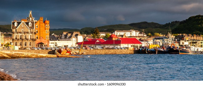 Oban, Scotland, UK - June 3, 2011: Sun shines on fishing boats and a wreck in the harbour at Oban in the West Highlands of Scotland.