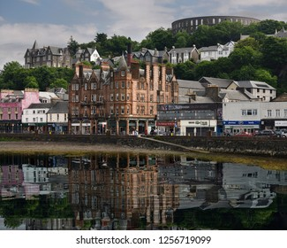 Oban, Scotland, UK - June 9, 2018: Historic buildings and McCaig's Tower on Battery Hill overlooking Oban harbour with water reflections in Oban Bay Scotland UK
