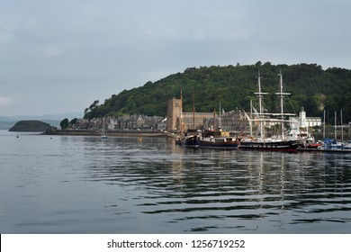 Oban, Scotland, UK - June 9, 2018: Sailing ships moored in Oban Harbour with St Columba's Cathedral on Oban Bay in the morning Scotland UK