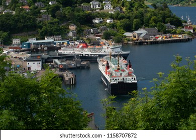 """Oban/Scotland - July 4th 2018: CalMac's ferry """"Isle of Mull"""" is seen leaving for Craignure, while MV """"Isle of Lewis"""" is arriving from Castlebay on the Isle of Barra in the Outer Hebrides,"""