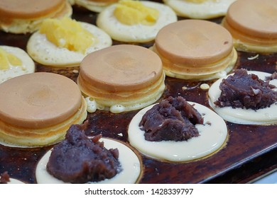 Obanyaki also known as Imagawayaki, Japanese dessert made from flour mixed with egg, cooked in pan stove and filled with custard cream, purple sweet potato and most popular is red bean.