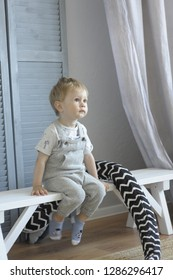 obedient child boy in light overalls sits on a bench and listens carefully and observes in room