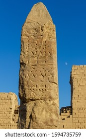 Obelisk with hieroglyphics at the temple of Karnak before a blue sky with moon