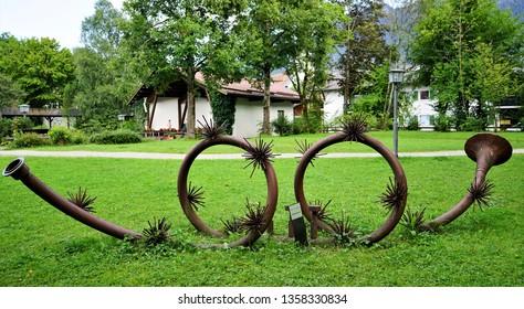 Oberamergau, Germany - August 2018: Very long spiral Alphorn displayed in grassy field.